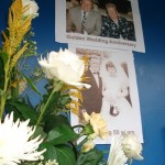 Close up of pedestal floral arrangement with happy anniversary posters