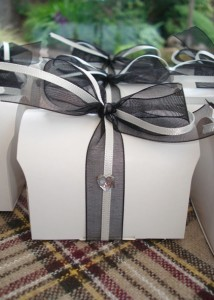 Off-white favour boxes filled with home-made tablet & table trivia, decorated with blank ribbon & heart diamante