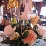 Table floral arrangement with photo at Golden Wedding Anniversary celebration